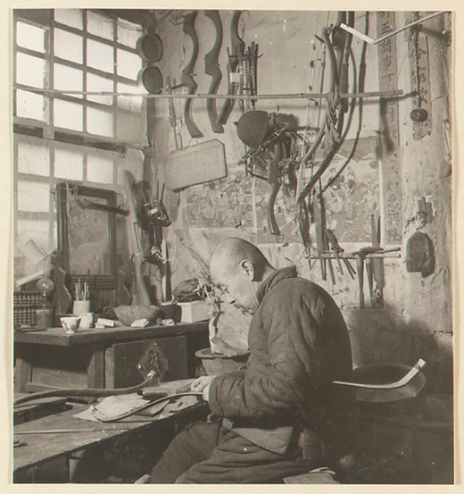 A man constructing a short monkey bow, some pellet crossbows can be seen on the wall behind him. Photo by Hedda Morrison at Ju Yuan Hao, Beijing, 1935.